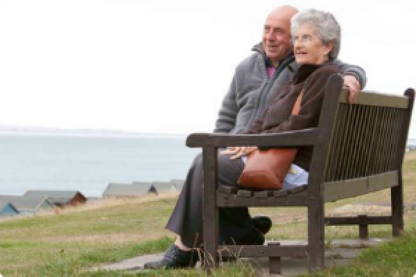 Image of elderly couple relaxing by the sea.